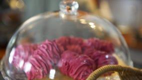 Feche acima para bolos cor-de-rosa da merengue sob a campânula de vidro na pastelaria francesa do café, conceito do alimento Arte video estoque