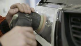 Feche acima para a cabeça lustrando e de lustro do auto mecânico do carro luz Arte Trabalhador que lustra o farol de um carro em vídeos de arquivo