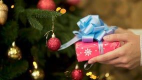 Feche acima para a mão fêmea que guarda o presente de Natal no papel de envolvimento vermelho com a fita grande, azul Mão da mulh vídeos de arquivo