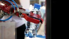 Feche acima para a mão vermelha do robô que guarda uma garrafa do wate no fundo borrado, conceito da inteligência artificial medi filme