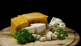 Feche acima para queijos envelhecidos deliciosos franceses choped e serviu na placa de madeira isolada no fundo preto Quadro vídeos de arquivo