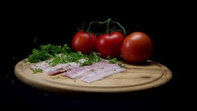 Feche acima para a salsa verde que cai em uma placa de madeira com fatias frescas de prosciutto, de tomates maduros e de hortaliç filme