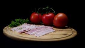 Feche acima para uma placa de madeira com fatias frescas de prosciutto, de tomates maduros e de hortaliças isolados no fundo pret filme
