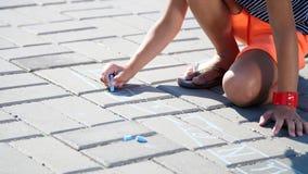 Feche acima, uma menina nos óculos de sol, desenhos da tração com os pastéis coloridos no asfalto, telhas da rua Um dia de verão  vídeos de arquivo