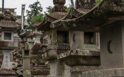 Feche até muitas lanternas de pedra diferentes na maneira a um templo budista em Japão Templo de Higo Honmyo, prefeitura de Kumam foto de stock royalty free