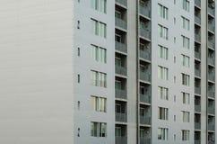 Feche até uma construção, teste padrão das janelas de uma construção cinzenta fotos de stock