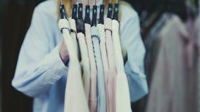 Feche da mulher bonita nova pega todas as blusas dos ganchos vídeos de arquivo