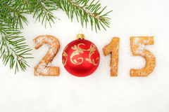 Feche el Año Nuevo de 2015 hechos en casa en nieve con el abeto con la chuchería roja Foto de archivo libre de regalías