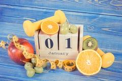 Feche el 1 de enero en calendario del cubo, las frutas, las pesas de gimnasia y la cinta métrica, Años Nuevos de concepto de las  Foto de archivo libre de regalías