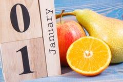 Feche el 1 de enero en calendario del cubo y las frutas frescas, concepto de resoluciones de los Años Nuevos de la nutrición sana Fotografía de archivo