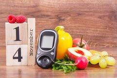 Feche el 14 de noviembre, el metro de la glucosa para comprobar el nivel y las frutas del azúcar con las verduras, el día de la d fotografía de archivo