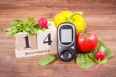 Feche el 14 de noviembre, el metro de la glucosa para comprobar el nivel y verduras del azúcar, el día de la diabetes del mundo y foto de archivo