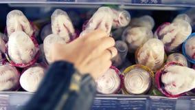 Feche extremamente acima da metragem de um gelado na prateleira no supermercado O mão-cliente fêmea toma um gelado e video estoque