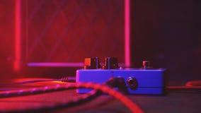 Feche extremamente acima do botão para pedal da guitarra do efeito o eletro Luz de néon vermelha no clube noturno durante o conce imagem de stock royalty free