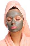 Feche a face da mulher nova com uma máscara da lama nela. Foto de Stock Royalty Free