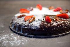 Feche la torta adornada con el azúcar, las fechas secas y las fresas frescas Imagen de archivo