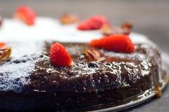 Feche la torta adornada con el azúcar, las fechas secas y las fresas frescas Fotos de archivo