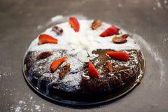 Feche la torta adornada con el azúcar, las fechas secas y las fresas frescas Imagen de archivo libre de regalías
