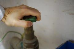 Feche o torneira - mãos na roda Foto de Stock Royalty Free