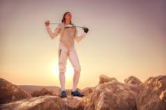 Fechtermann, der auf den Felsen steht und seine Klinge auf den Schultern hält Lizenzfreies Stockfoto