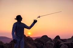 Fechtermann, der oben seine Fechtenklinge auf einem Hintergrund des Sonnenunterganghimmels und -felsen wirft Stockfotos
