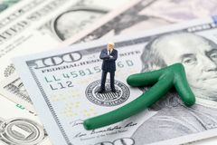 FED consider interest rate hike, world economics and inflation c. Ontrol, miniature businessman leader standing on US Federal Reserve emblem on dollars banknote royalty free stock images