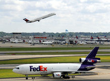 Fed Ex plane at Atlanta airport. A Fed Ex cargo plane taxiing on a runway with a Delta jet  taking off in the background at Atlanta Hartsfield Jackson airport Stock Image
