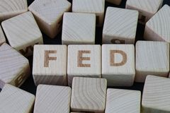 FED, Federal Reserve concept, cube wooden block with alphabet building the word FED at the center on dark blackboard background,. The institution to control US stock images