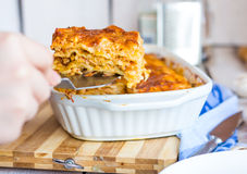 Fed meat lasagna on a white plate, hand Stock Images