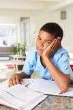 Fed Up Boy Doing Homework en cocina foto de archivo