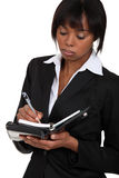 Fed-up businesswoman. Writing in her agenda Stock Photos