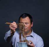 Fed up with chopsticks. Guy getting pretty fed up with his attempts on eating with chopsticks Royalty Free Stock Photo