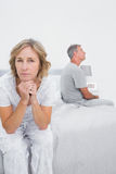 Fed up couple sitting on different sides of bed having a dispute Royalty Free Stock Images