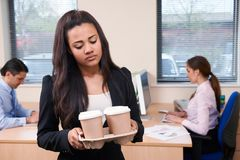 Fed Up Female Intern Fetching Coffee In Office. Fed Up Female Intern Fetches Coffee In Office Stock Photo