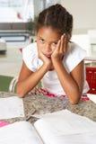 Fed Up Girl Doing Homework en cocina fotos de archivo libres de regalías