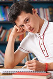 Fed Up Male Teenage Student che lavora nella biblioteca Fotografie Stock Libere da Diritti