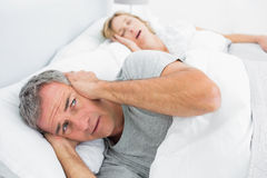 Fed up man blocking his ears from noise of wife snoring. Fed up men blocking his ears from noise of wife snoring at home in bedroom royalty free stock images