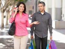 Fed Up Man Carrying Partners-Einkaufstaschen auf Stadt-Straße Stockfotos