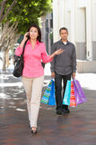 Fed Up Man Carrying Partners-het Winkelen Zakken op Stadsstraat royalty-vrije stock afbeelding