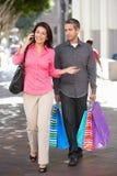 Fed Up Man Carrying Partners-het Winkelen Zakken op Stadsstraat stock afbeeldingen