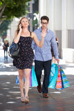 Fed Up Man Carrying Partners Shopping Bags On City Street. Walking Stock Photo