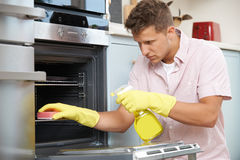Fed Up Man Cleaning Oven thuis royalty-vrije stock afbeelding