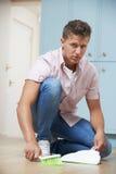 Fed Up Man Sweeping Floor con la paletta per la spazzatura e la spazzola Fotografie Stock Libere da Diritti