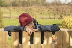 Fed up mature woman outdoors. Resting on fence royalty free stock photography