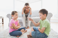 Fed up mother listening to her young children argue Stock Images