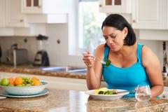 Fed Up Overweight Woman Eating sunt mål i kök royaltyfria bilder