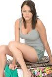 Fed Up Stressed Young Woman triste che si siede su una valigia piena di straripamento immagine stock