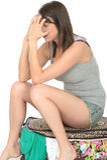 Fed Up Stressed Young Woman triste que se sienta en una maleta llena que desborda imagenes de archivo