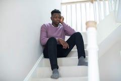 Fed Up Teenage Boy Sitting en las escaleras en casa imagenes de archivo