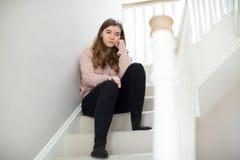 Fed Up Teenage Girl Sitting en las escaleras en casa fotografía de archivo